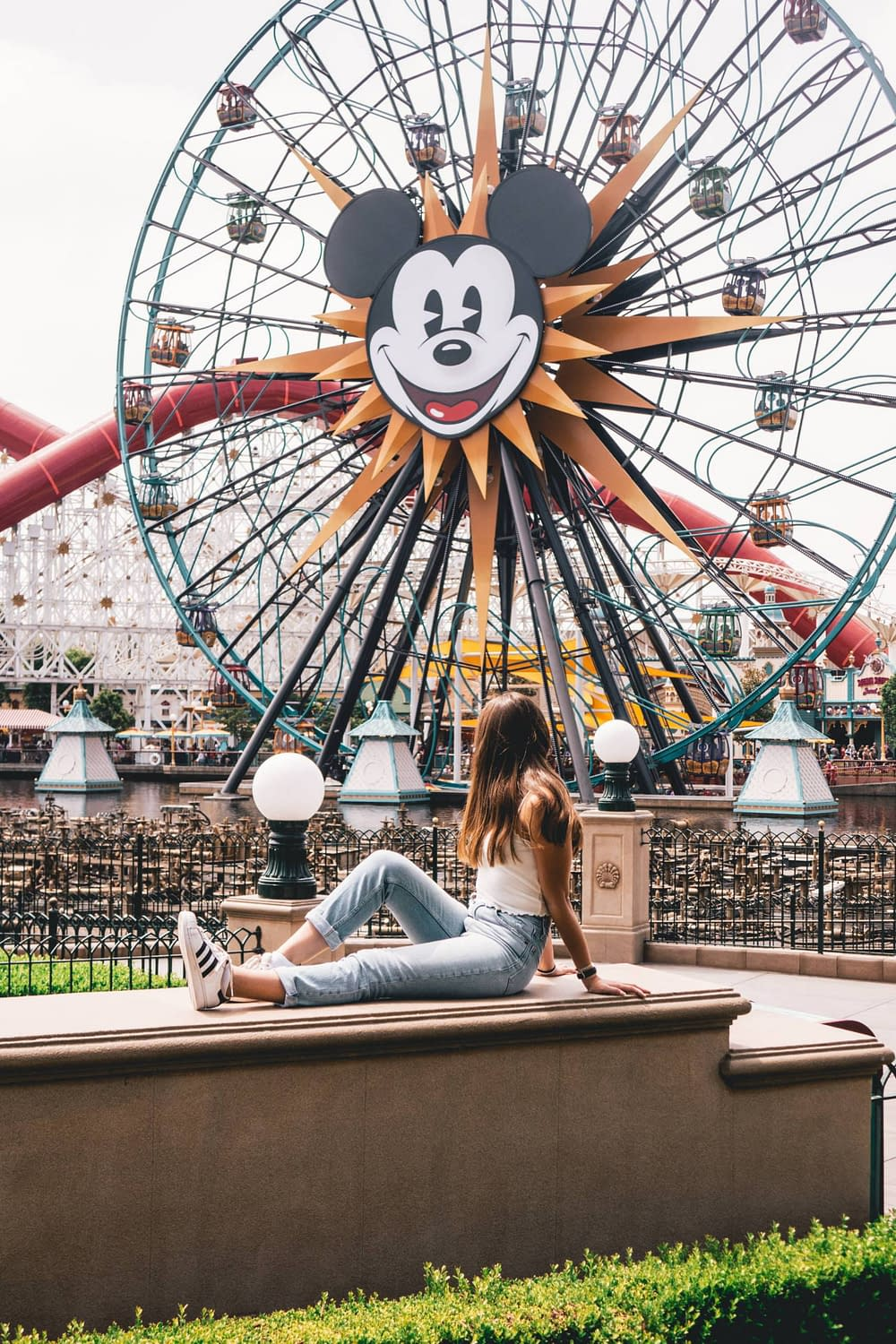 A girl posing in front of the Mickey Mouse Ferris Wheel in Disneyland California.