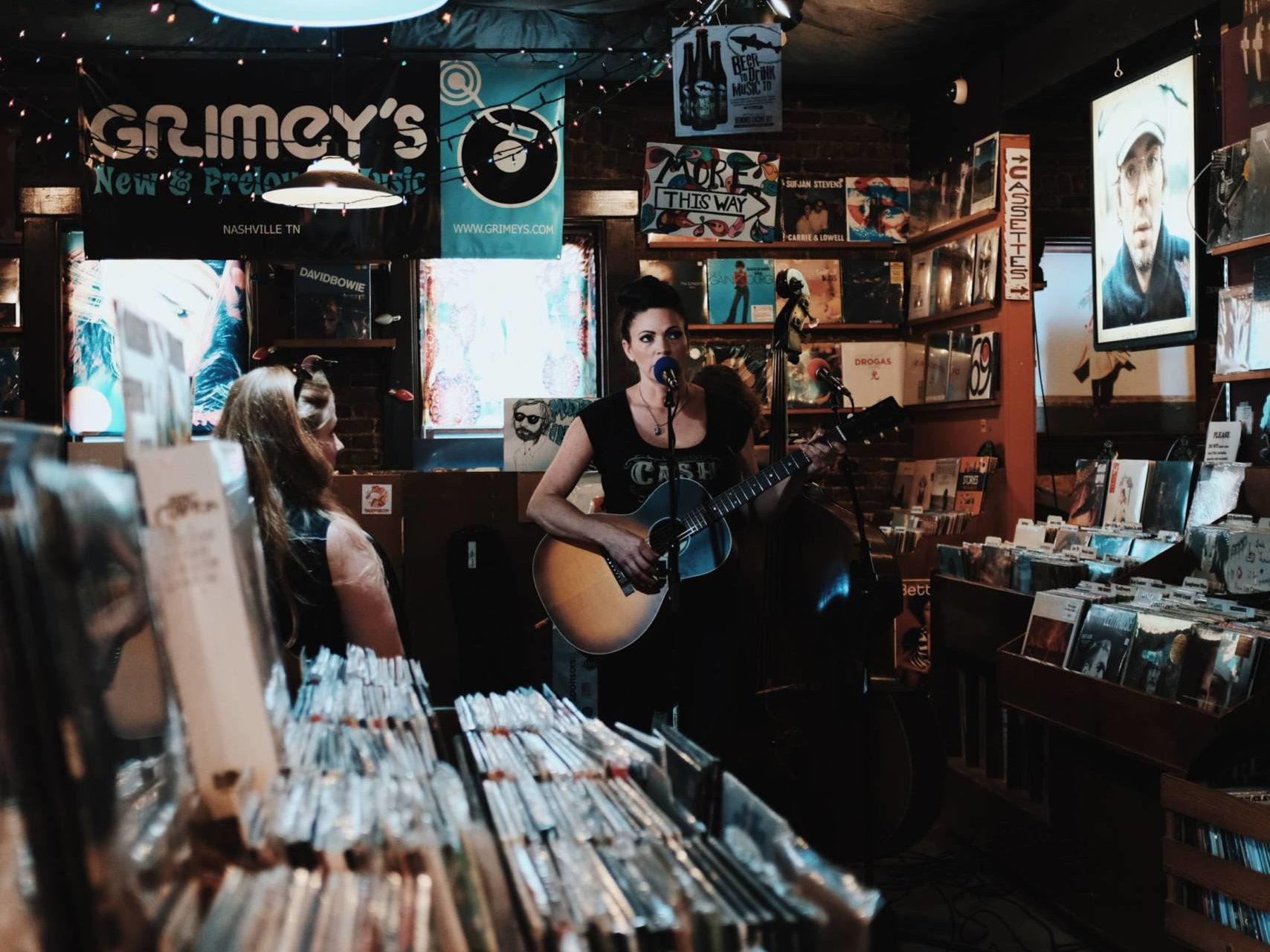 A musician in a record shop is playing her Guitar