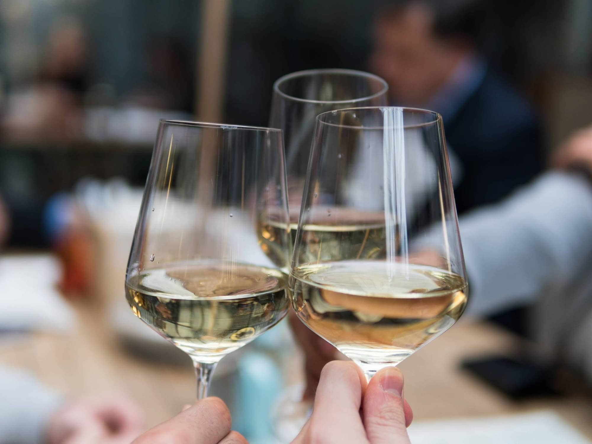 A cheers of white wine