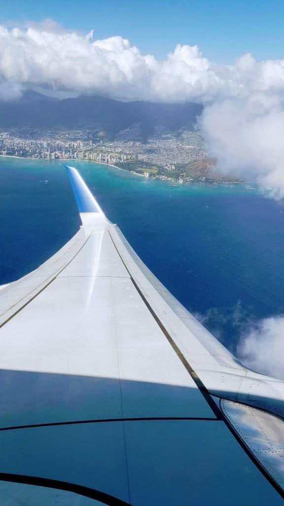 An over-wing shot of an aircraft coming in for approach into an island.