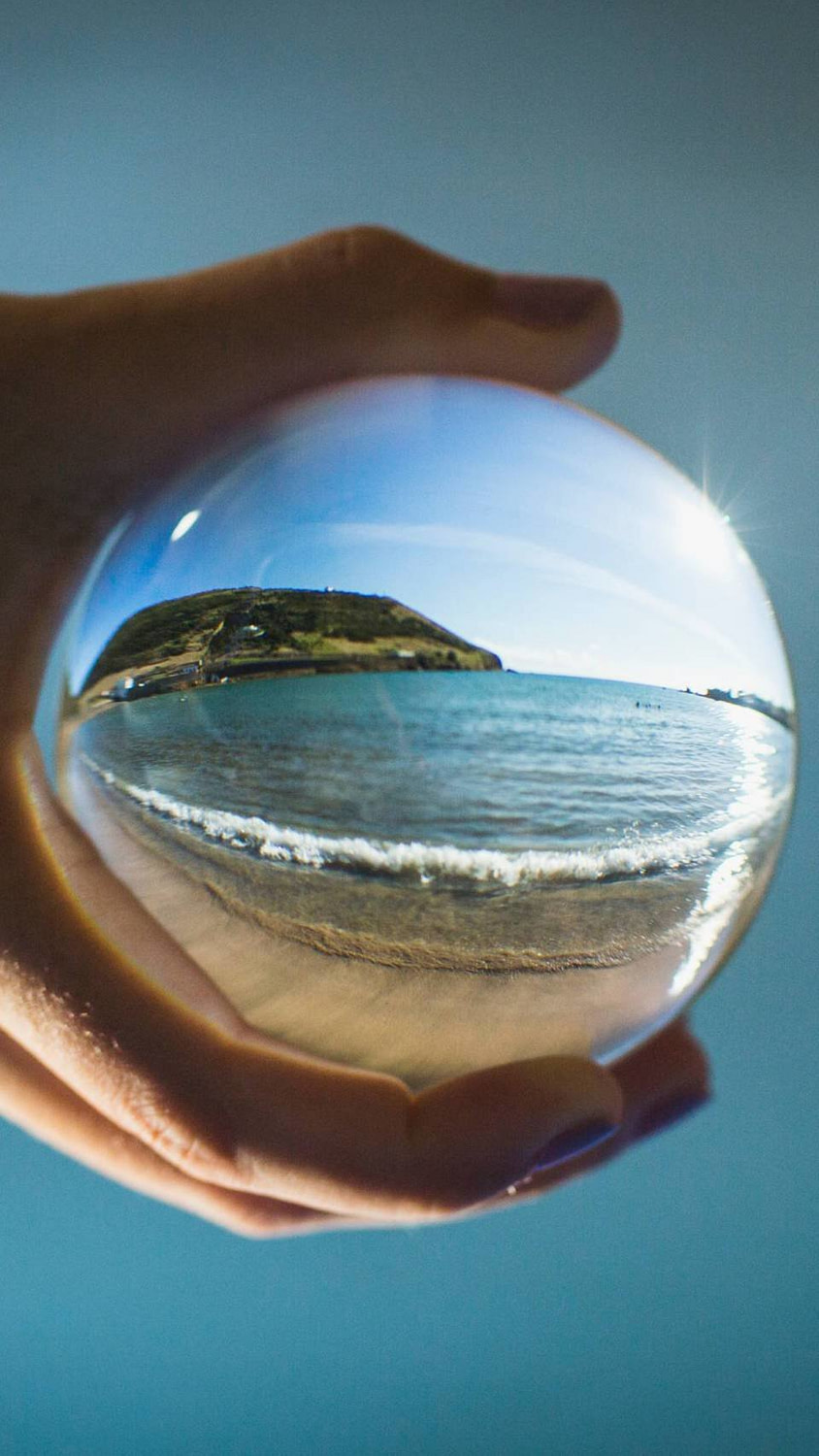A look through a glass ball refracting a close up shot of the beach on Faial